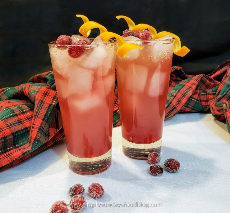 Two tall ice filled glasses of cranberry and orange juices with a shot of vodka and topped with champagne.  Garnished with sugared cranberries and orange twists on a white cloth with a red and green plaid runner