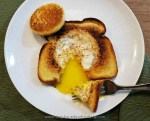 Lightly toasted potato bread with a fried egg cooked in the center of it where a hole was punched out. There is a silver fork with a piece of toast and egg on it on the plate which is white. The golden yellow yolk is leaking out of the egg onto the plate and the hole that was punched out is also toasted and balanced on the toast. The plate is on a wooden cutting board with a green cloth under half