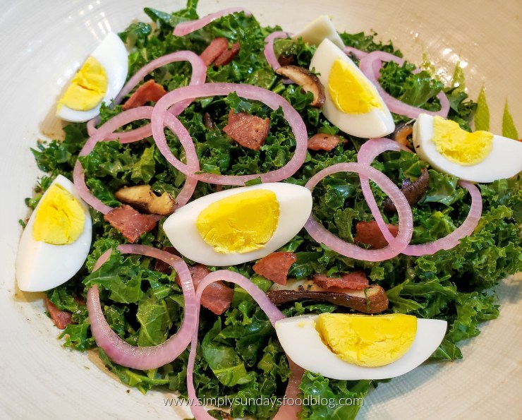 A large serving bowl with kale salad topped with pickled onions, hard cooked eggs and loaded with turkey bacon and shiitake mushrooms