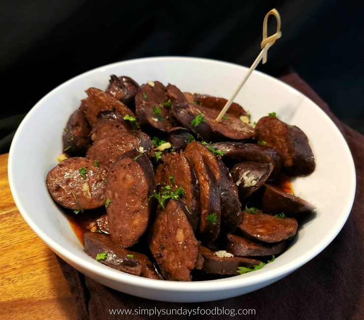 A white bowl on a wood board with a black background. In the bowl are shiny slices of reddish brown chorizo sausage with a darker casing around them. Ther are sprinkled with fresh green parsley and grated white garlic. There is a bamboo toothpick with a twisted head sticking out of one of the sausage slice