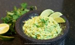 A bowl with guacamole garnished with cilantro and fresh lime wedges