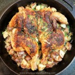 A brown and crispy skinned spatchcocked and roasted chicken sitting on a bed of roasted red skin potatoes and roasted onions in a black cast iron pan sprinkled with fresh green parsley