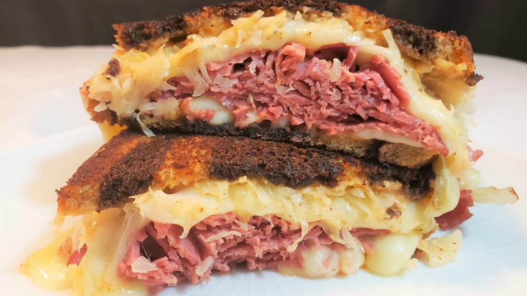 Two halves of a reuben sandwich stacked on top of each other with melting cheese, corned beef and kraut