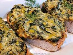 Salmon steaks on a white serving platter topped with a creamy sauce loaded with leeks and swiss chard and green sprigs of fresh dill