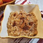 Steel cut apple oats in a square casserole dish garnished with pecans on a red and white striped cloth
