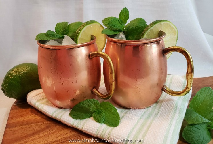 Two chilled copper mugs on a cloth filled with the moscow mule cocktail and garnished with fresh mint and lime wheels