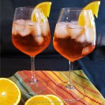 Two glasses of Aperol Spritz Cocktails garnished with orange wheels on a colorful napkin