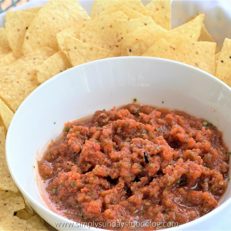 A bowl of fire roasted salsa on a bed of crunchy tortilla chips