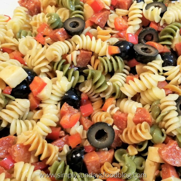 A close up photo of spicy pepperoni & creamy Parmesan cheese tossed into festively colored pasta and all mixed with a zesty homemade balsamic vinaigrette