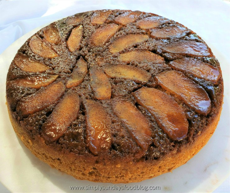 A brown spice cake sitting on a white dish with a white background topped with caramelized sauce and apples in a fan shape