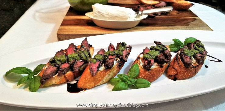 Medium rare sliced skirt steak on crusty toasted baguette slices topped with fresh green basil pesto and drizzled with reduced balsamic vinegar on a white serving platter