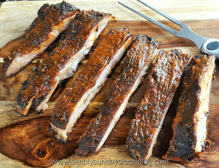 Tender ribs glazed with a deep red brown barbeque sauce on a wooden cutting board