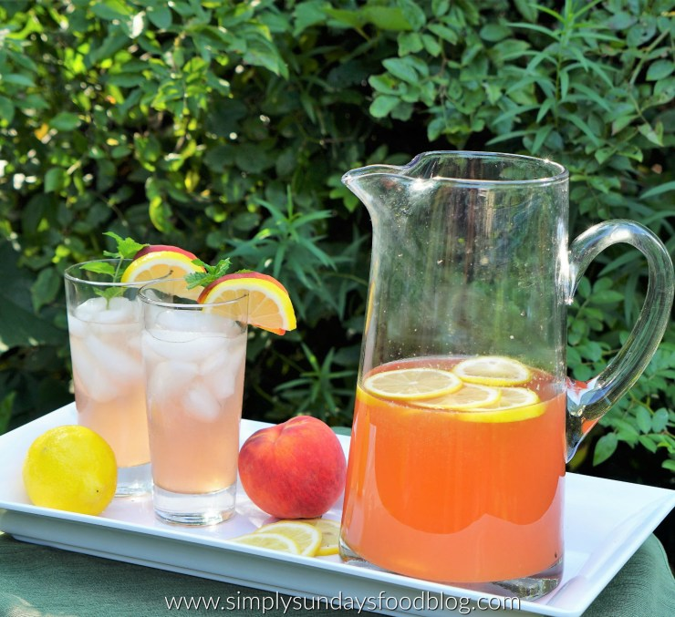 Two ice cold glasses of peach lemonade next to a pitcher and fresh lemons and peaches. Greenery in the background
