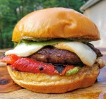 CLose up photo of a portabella burger on a roll with roasted red peppers, basil pesto, smoked mozzarella and greens