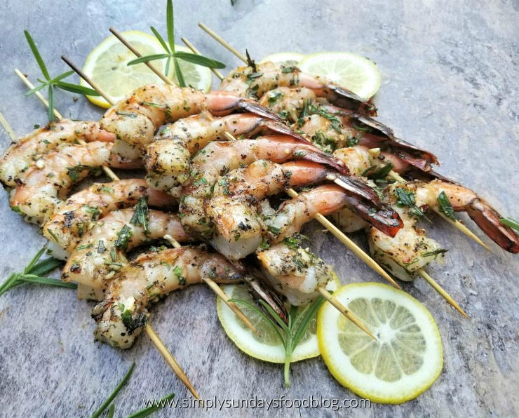 Shrimp threaded on wooden skewers over fresh rosemary and lemon slices