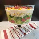 Layers of crisp vegetables topped with a creamy dressing, sharp cheddar and salty bacon in a trifle bowl