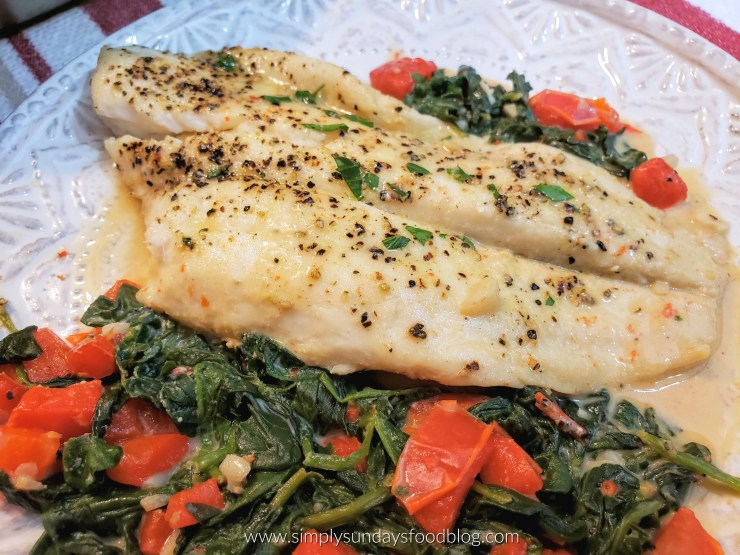 Flounder on a bed of spinach and tomatoes in a lightened cream sauce