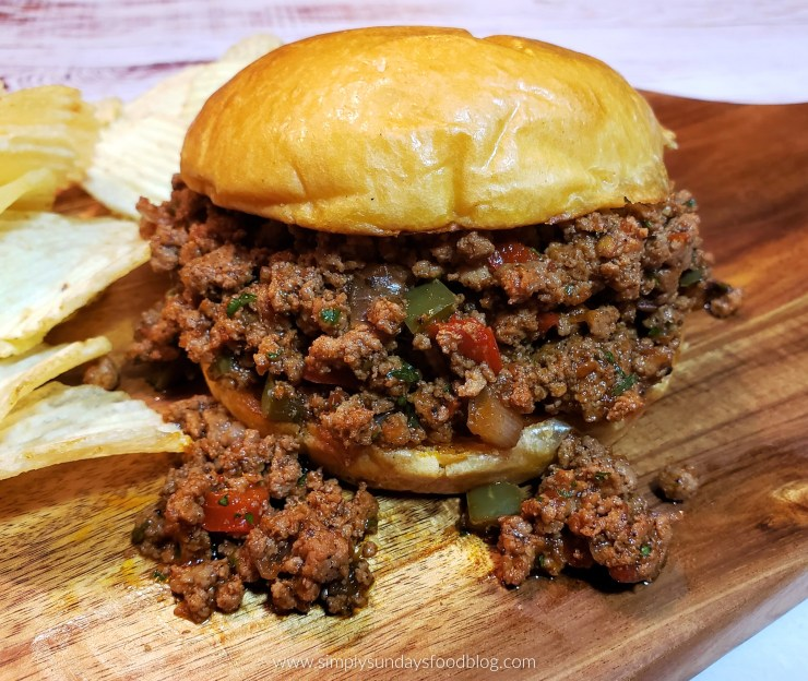 Ground meat in a rich brown sauce speckled with diced red and green bell peppers on a toasted brioche roll on a wooden cutting board with potato chips on the side
