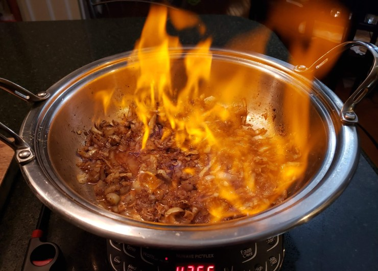 Brandy being flambeed in the pan so a big flame is cooking off the alcohol