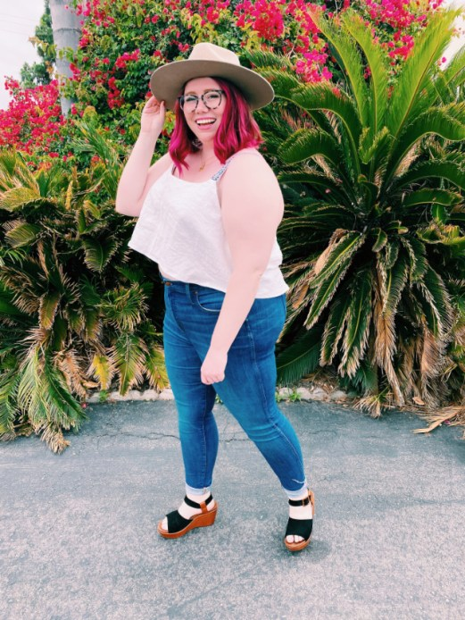 Curvy girl with magenta hair poses on street with white handmade top by sewing.