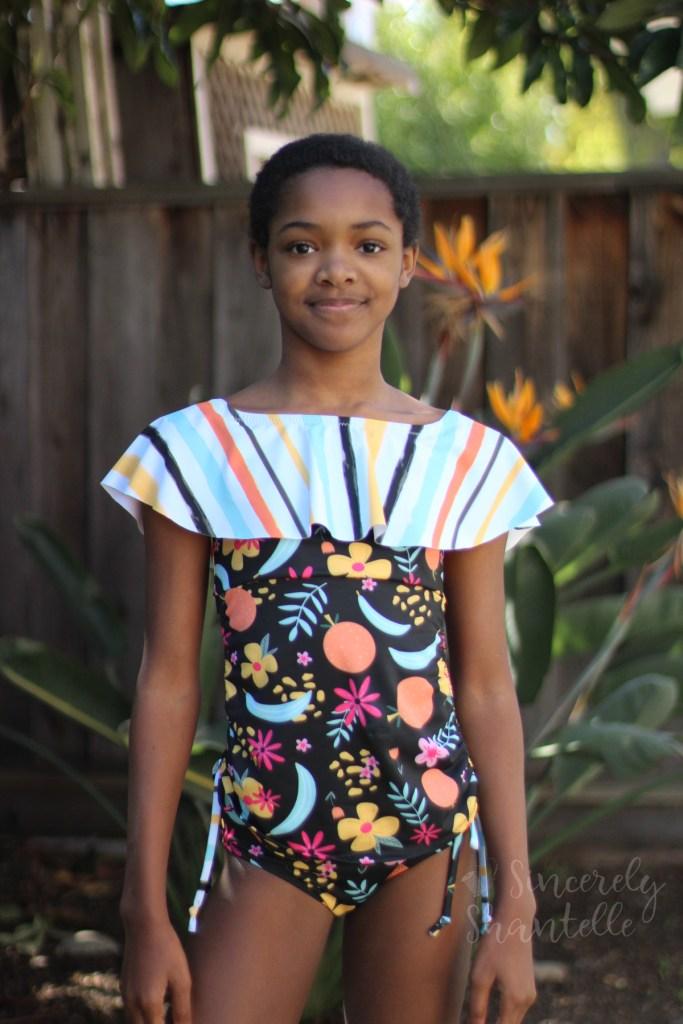 girl wearing black fruity floral swimsuit
