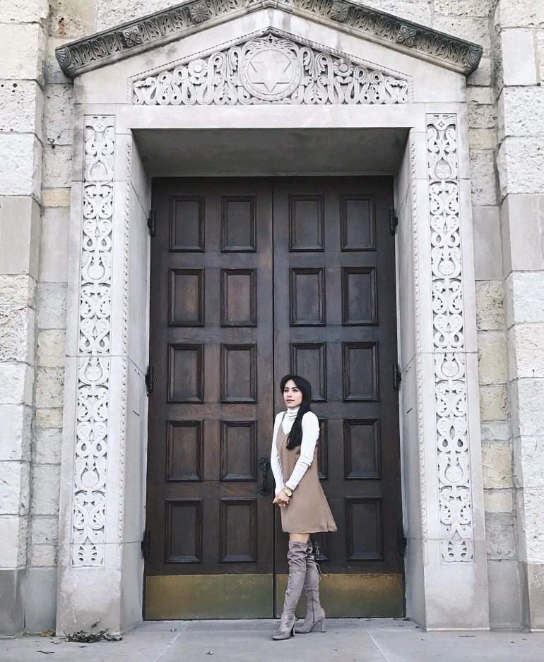 neutral slip dress layered over an ivory turtleneck and taupe over-the-knee boots