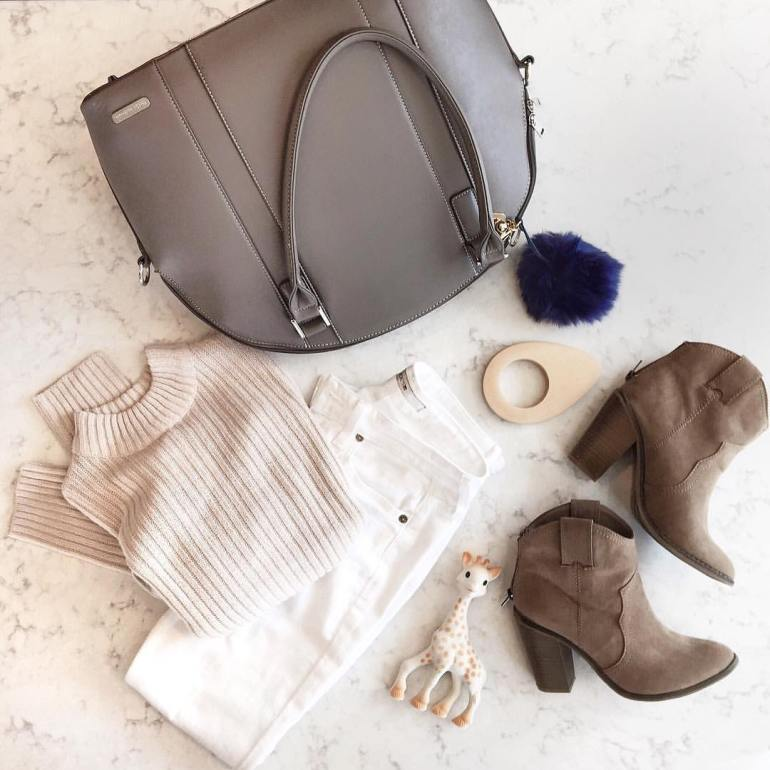 flat lay of diaper bag, wardrobe essential ankle boots, white denim, beige sweater, and baby teethers