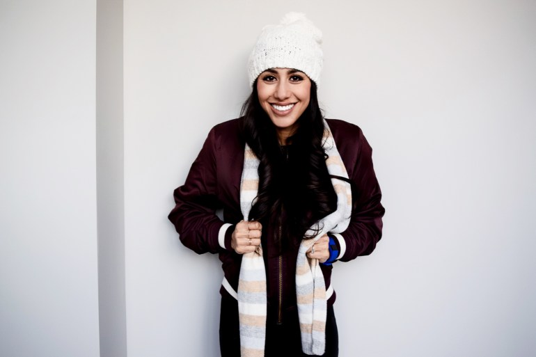woman wearing white pom beanie, burgundy bomber, black faux leather leggings, white scarf, and rose gold nikes air max theas