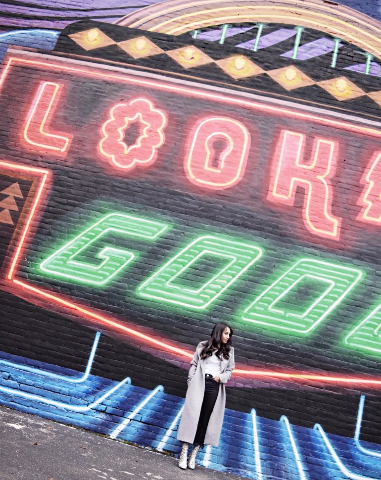 brunette woman wearing gray duster coat, black fringe jeans, sparkle ankle boots in front of a city mural