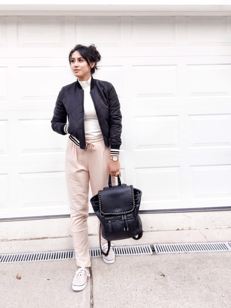 black bomber jacket, blush joggers, camel sneakers, black faux leather backpack