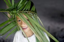 A young Mentawai boy poses with a palm frond hat being woven for a local school orientation day. Copyright: Palmer Keen