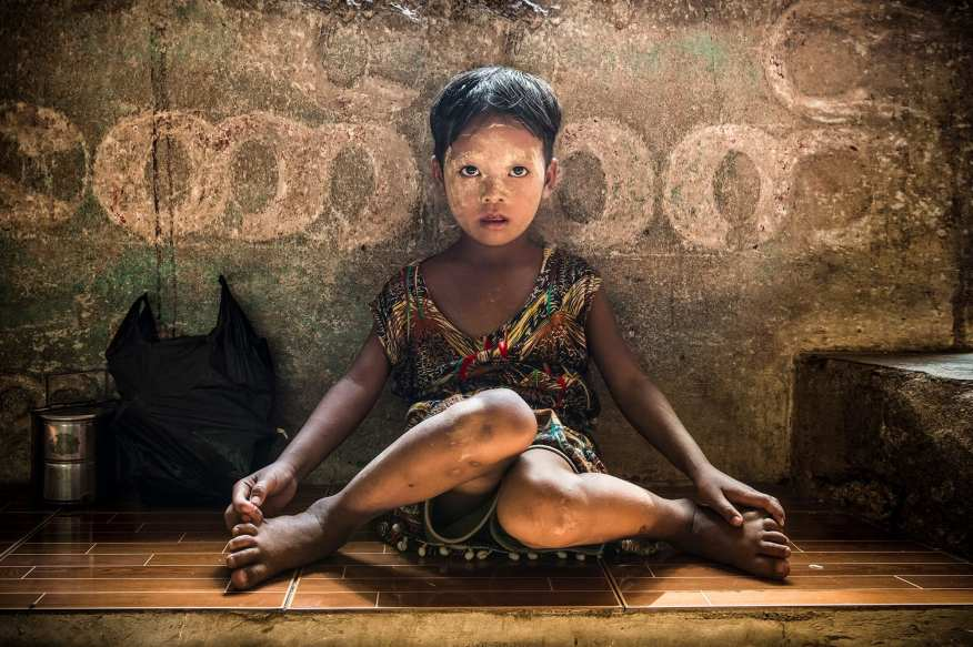 """2ND PLACE PORTRAIT - Paolo lo Pinto. """"The warm light of the Burmese sunset, the face of a child colored by the Thanaka, two wonderful eyes ... the recipe for a magical moment."""" I was waiting for the train that would take me back to Yangon, tired and sleepy i was sitting on a crumbling bench when suddenly my gaze was captured by this wonderful girl who was waiting for the train with her mother. She had two magnetic eyes made even more unique by Thanaka's doused face. The Thanaka is a yellowish-white cosmetic paste made from ground bark. It is a distinctive feature of the culture of Myanmar applied by women and girls to the face and sometimes to arms. Next to her there was her lunch box and an her favorite games that she was bringing to school. When I approach her offering candies her face lit up and she start smiling and hiding behind her Mom's dress. She was also intrigued by my camera so I asked her Mom if I could take a picture of her in order to show her how the camera works. Her face, the warm light filtered from the roof of the station created a fantastic portrait so much to excite me every time i looked at it. I showed them the picture and their faces were pervaded with amazement never seen before."""