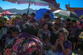 The Perez family, direct descendants of the Tzotzil Maya, sit around the tomb of their mother as they wait for the higher priest to arrive and perform a prayer. During Dia de los Muertos, all members of the community gather at the local cemetery atop the mountains and wait as the priest prays to each individual tomb in the Tzotzil language. Once the priest has visited all the tombs, they all descend together back to town.
