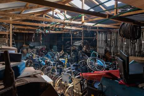 Broken wheelchairs in a shed behind the Joytown Special School. Sometimes volunteers come in to try and assemble new wheelchairs out of parts that might still be good. The average lifespan of a wheelchair is around 5 to 6 years but in Thika it\'s only about two because of the bad surface where the school is built and the fact that they constantly have to be modified for each child.
