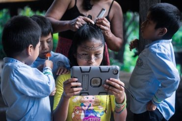 Leyli Gualinga, 11, plays with an iPad while her mother Marcia GUalinga combs her hair and her brothers watch her.