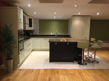 Kitchen redesign- black kitchen island, green roller blind
