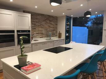 Contemporary new kitchen with brick splashback & teal coloured counter stools