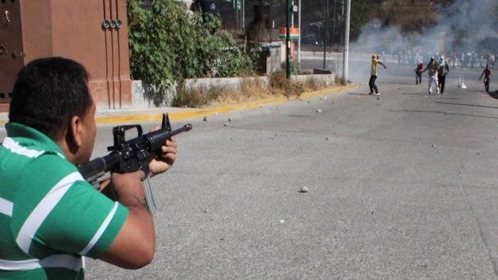 Presunto Policía ministerial apuntó con su fusil de asalto a normalistas durante el bloqueo del 12 de diciembre de 2011. Foto: Cuartoscuro