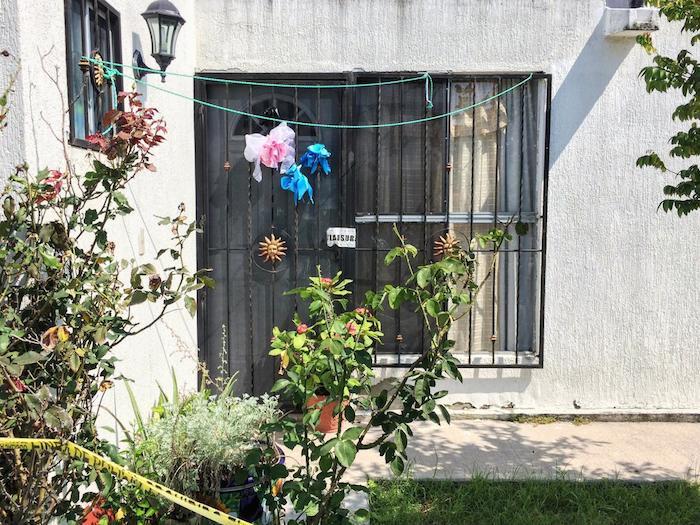 Así luce la casa de Sol, Alberto y Óscar: un moño rosa y dos azules representan a quienes habitaron este hogar. Foto: VICE News