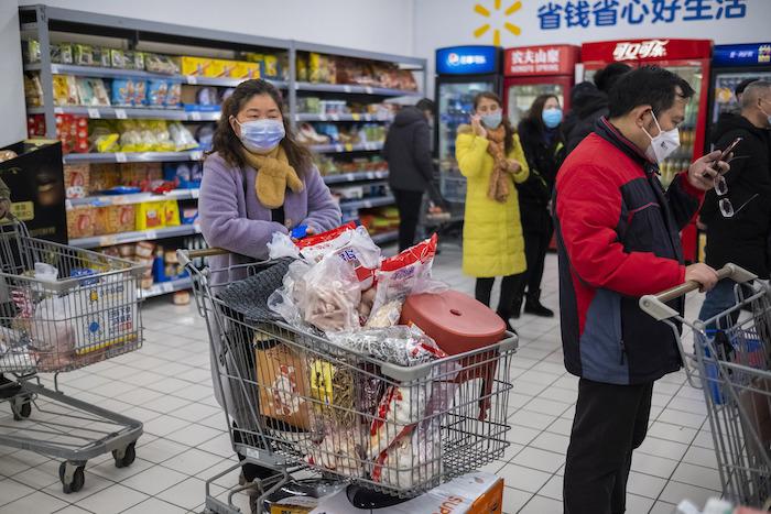 En esta foto del 22 de enero de 2020, clientes con cubrebocas hacen compras en una verdulería en Wuhan, China. La cuarentena debido al brote de coronavirus complica la logística de enviar alimentos y otros bienes a 50 millones de chinos. Foto: Arek Rataj, AP