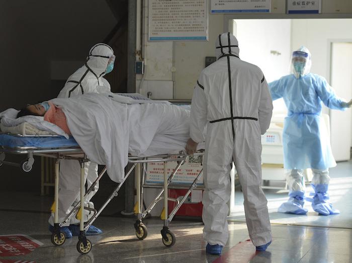 Personal médico, vestidos con trajes de protección, trasladan a un paciente afectado por un coronavirus a una zona de aislamiento en un hospital de Fuyang, en la provincia de Anhui, en el centro de China, el 1 de febrero de 2020. Foto: Chinatopix vía AP