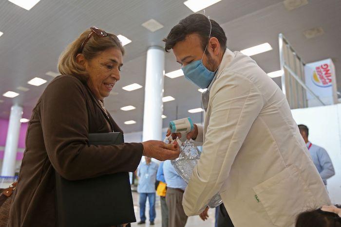 Un hombre pone gel antibacterial en las manos de una mujer, en el aeropuerto de Guadalajara. Foto: Fernando Carranza, Cuartoscuro