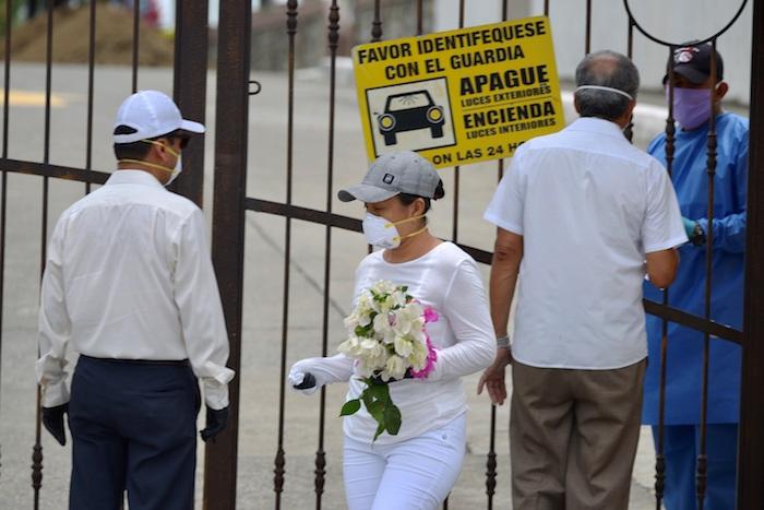 Familiares con tapabocas hacen consultas este miércoles a un guardia de seguridad de un cementerio, para poder despedir a sus seres queridos, en Guayaquil (Ecuador). Foto: Marcos Pin, EFE