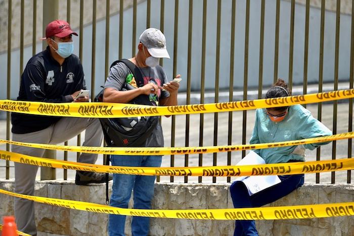 Familiares con tapabocas esperan este miércoles la llegada de los féretros con sus seres queridos a un cementerio de Guayaquil (Ecuador). Foto: Marcos Pin, EFE