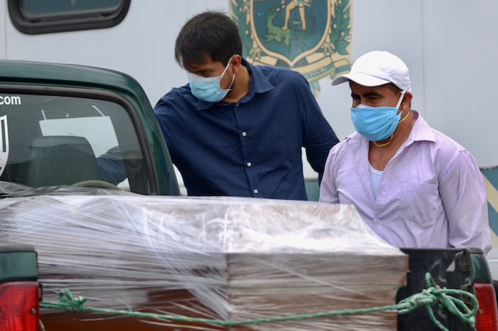 Familiares observan este miércoles el féretro de su ser querido fallecido a causa del coronavirus COVID-19, a su llegada a un cementerio de Guayaquil (Ecuador). Foto: Marcos Pin, EFE