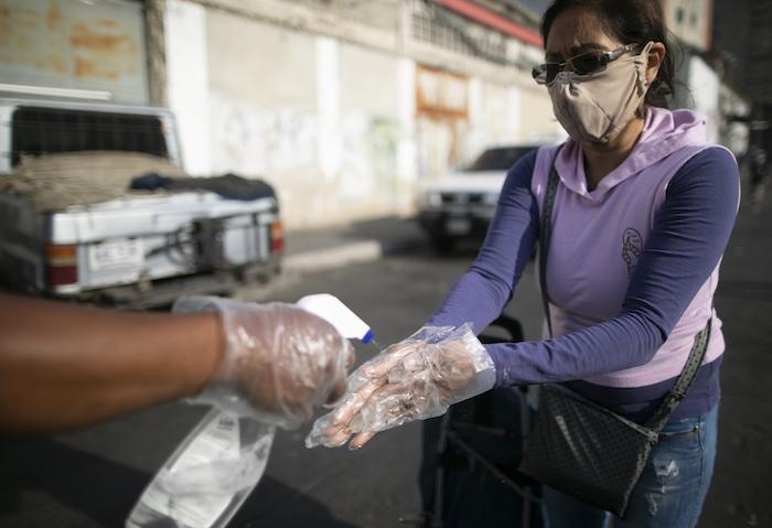 Las manos de una compradora son desinfectadas para evitar se contagie del coronavirus antes de entrar a un mercado callejero en Caracas, Venezuela, el viernes 10 de abril de 2020.