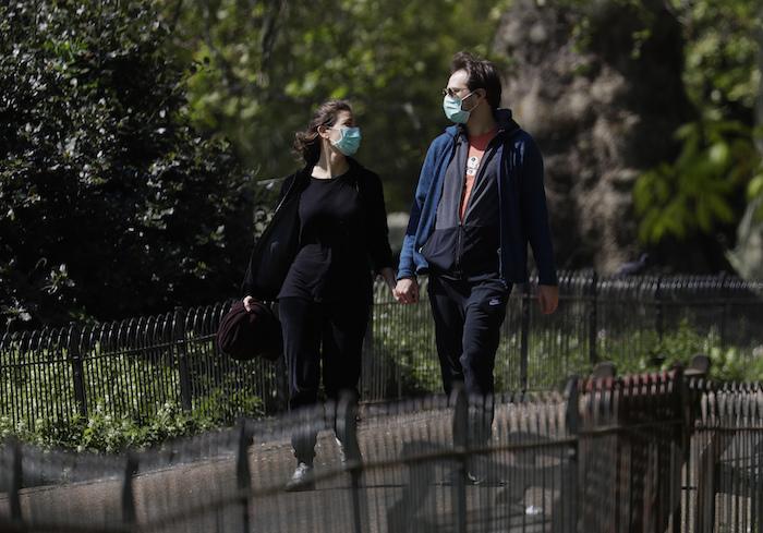 Unas personas con mascarillas caminan por el parque St. James en Londres, mientras el país sigue en confinamiento para ayudar a frenar la propagación del nuevo coronavirus, el domingo 19 de abril de 2020.
