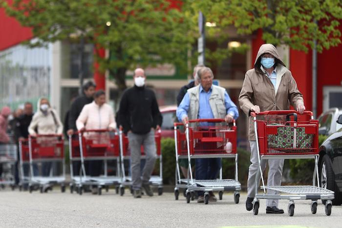 Una fila de personas con mascarillas esperando a entrar a una tienda en Munich, Alemania, el 20 de abril del 2020.