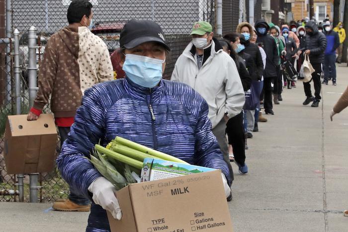 Una mujer se lleva una caja con comida mientras cientos de personas siguen haciendo cola en un centro de asistencia a los necesitados en Chelsea, Massachusetts, el 22 de abril del 2020. Chelsa es un suburbio de Boston mayormente hispano con la concentración de casos de coronavirus más grande de Massachusetts.