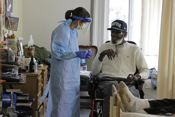 Fotografía del 17 de abril de 2020 de la doctora Gabrielle Beger preparándose para tomar una muestra nasal de Lawrence McGee como parte del equipo de médicos de la Universidad de Washington que realiza pruebas para el nuevo coronavirus en el albergue de ancianos Queen Anne Healthcare en Seattle.